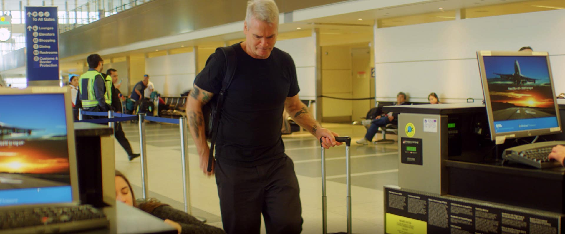 Henry Rollins packs light and weighs his luggage at Tom Bradley International in LAX