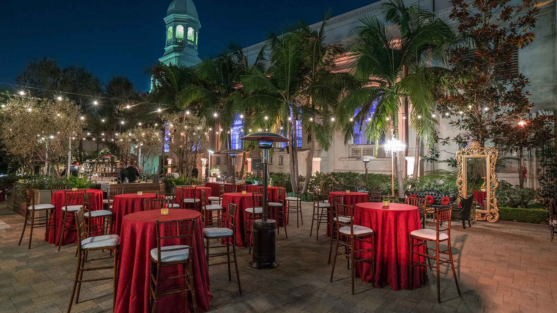 Red tables in courtyard at outdoor dining event