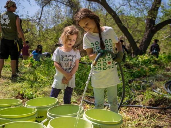 TreePeople two girls filling water buckets
