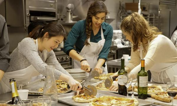 Three people cutting pizza at the Institute of Culinary Education's Couples Pizza and Wine Bar class.