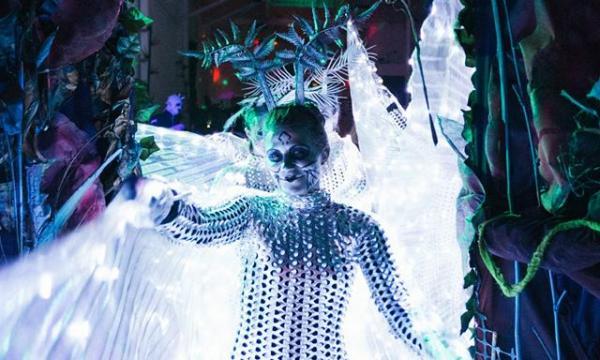 Glowing alien creature walking through party