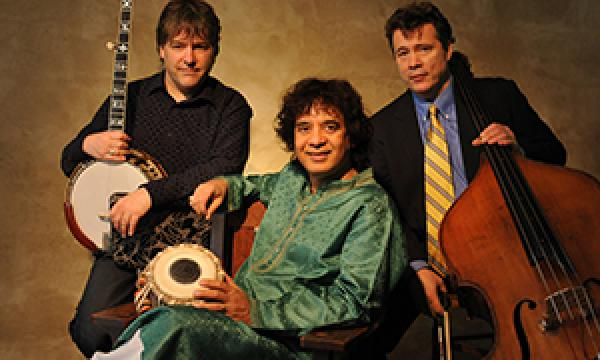 Bela Fleck, Zakir Hussain, and Edgar Meyer posing for a picture with their instruments in front of a rustic background.