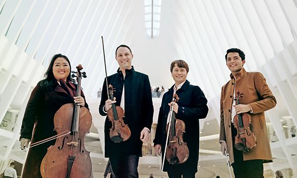 Estelle Choi, Ryan Meehan, Jeremy Berry, and Jeffrey Myers holding their respective instruments all the while posing in a well-lit concert hall