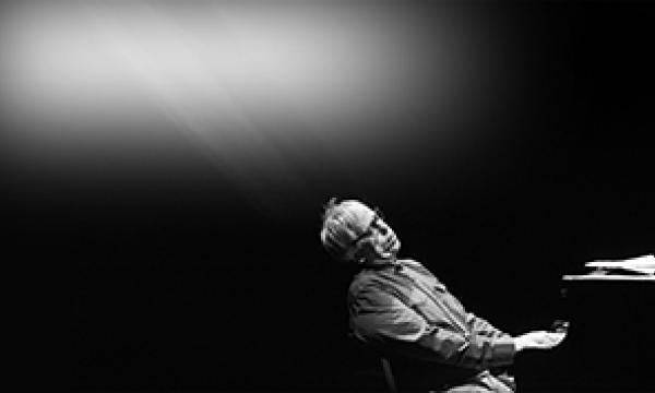 Black and white picture. Kenny Werner dramatically playing piano, leaning back enveloped by the music with a single stream of light from above illuminating his face and hands.