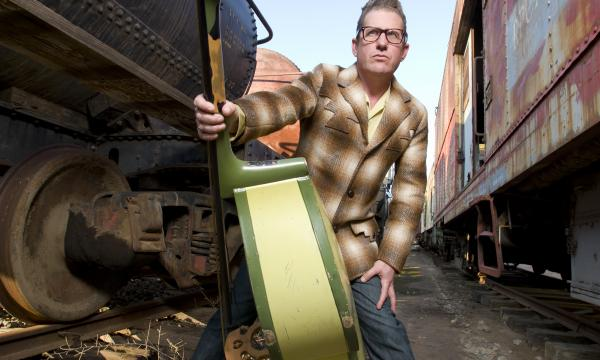 Lee Rocker holding a green bass in between two train cars.