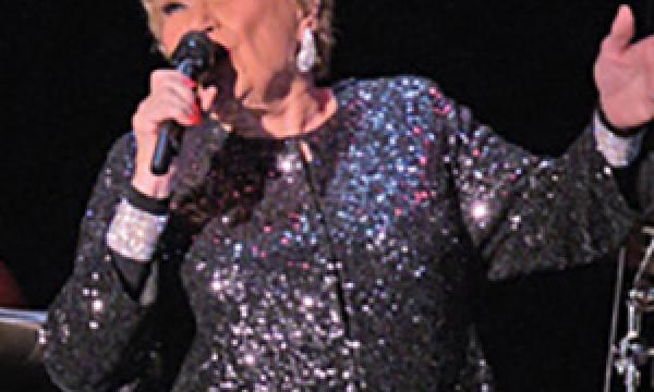 Grammy-Award nominated Marilyn Maye singing on stage in front of a black background.