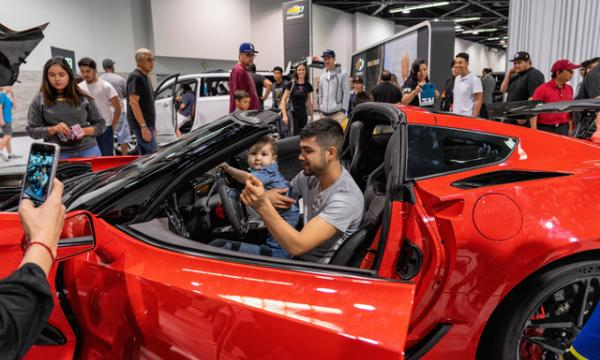 A family checks out a car at the Orange County International Auto Show.