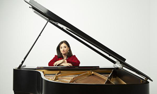 Renee sitting behind a beautiful black piano against a white background.