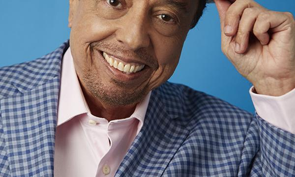Bossa Nova star, Sergio Mendes gently smiling and touching his hat against a blue background.