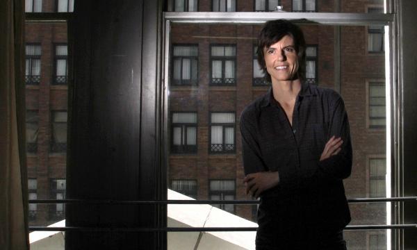 Tig Notaro in a city apartment, smiling.