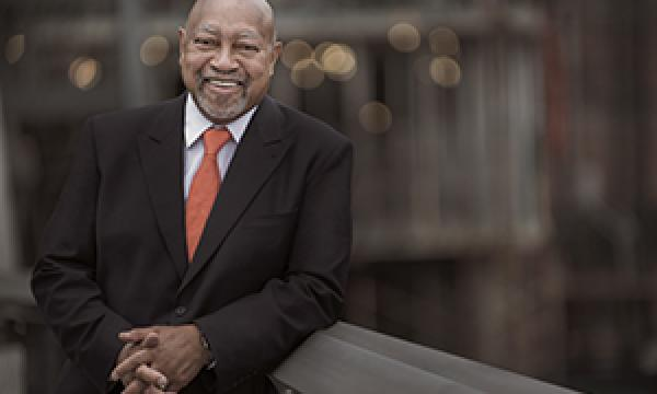 Jazz Master Kenny Barron smiling jovially against a blurred cityscape background.