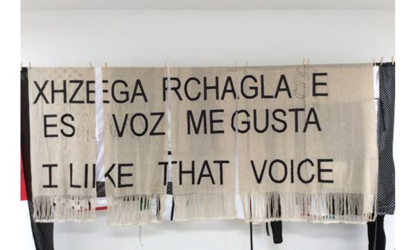 """Image of a rectangular textile piece with the words """"Xhzega rchaglase esa voz me gusta"""" and """"I like that voice"""" written across it."""