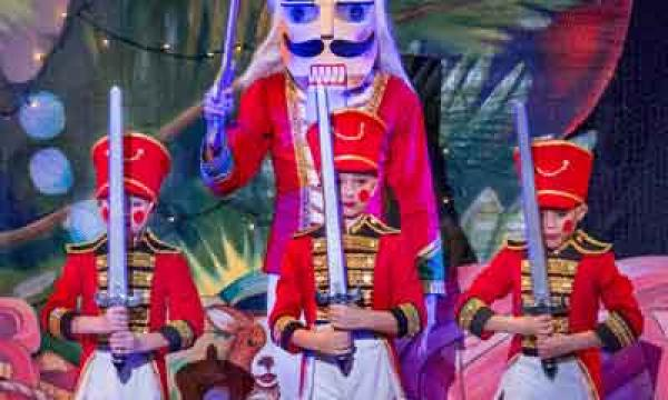 Dancer dressed as a Nutcracker, holding a sword and standing behind three children dressed as toy soldiers.