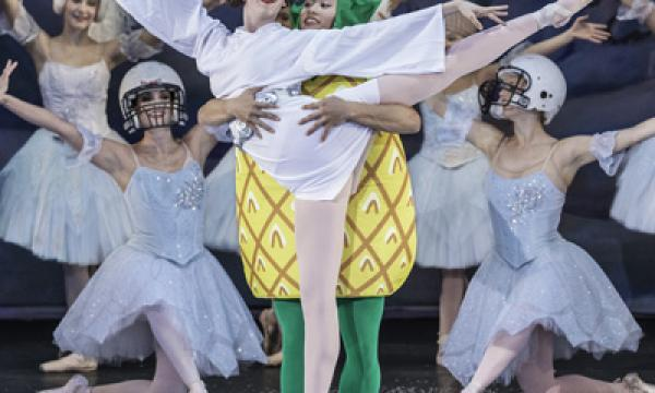 Dancer in a pineapple suit stands behind a ballerina.