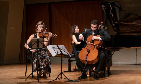 A violinist and a cellist are seated in front of a grand pianist.