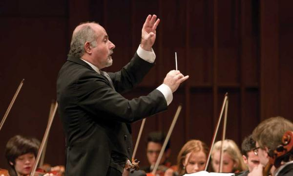 An old white man has his arms up conducting, holding a conducting baton.