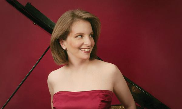 A white woman smiles in front of an open grand piano.