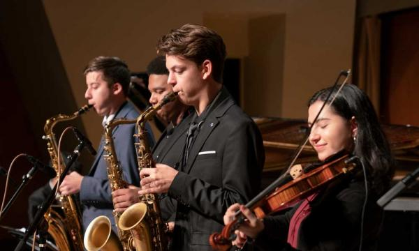 Three young people playing saxophones and one playing violin.