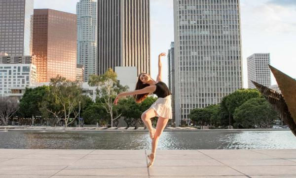 Ballet dancer pirouetting in front of Los Angeles skyline.