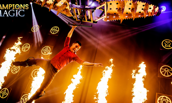 A man leaping across the stage with tremendous fire spewing behind him.