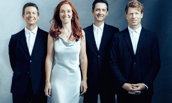 The four members of the Calder Quartet, dressed formally, are smiling at the camera.