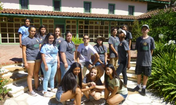 Teen training session, volunteers posing in the courtyard in front of the sunporch