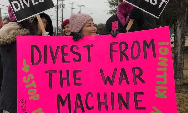 """At a protest, a woman is standing in front of two people who are holding a paper with """"DIVEST"""" printed on it and is attached to a stick each. The woman is holding a larger pink poster that reads """"Divest From the War Machine"""" in black, """"Stop Making a Killing on Killing!"""" in green, and """"@codepink"""" in much smaller print."""