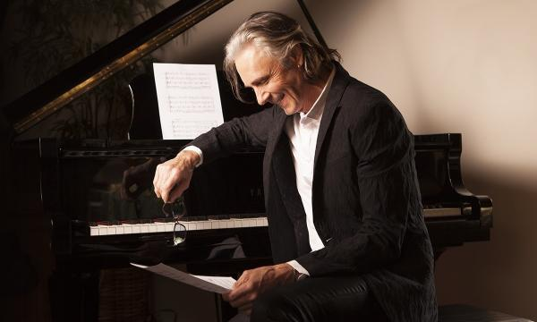 Rick Springfield sitting at a piano, smiling down at a sheet of music.