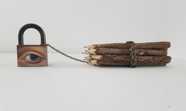 [Alexandra Dillon, The Burden of Drawing, 2020. Oil on big padlock, rustic pencils, chain. 15 x 2 in.]