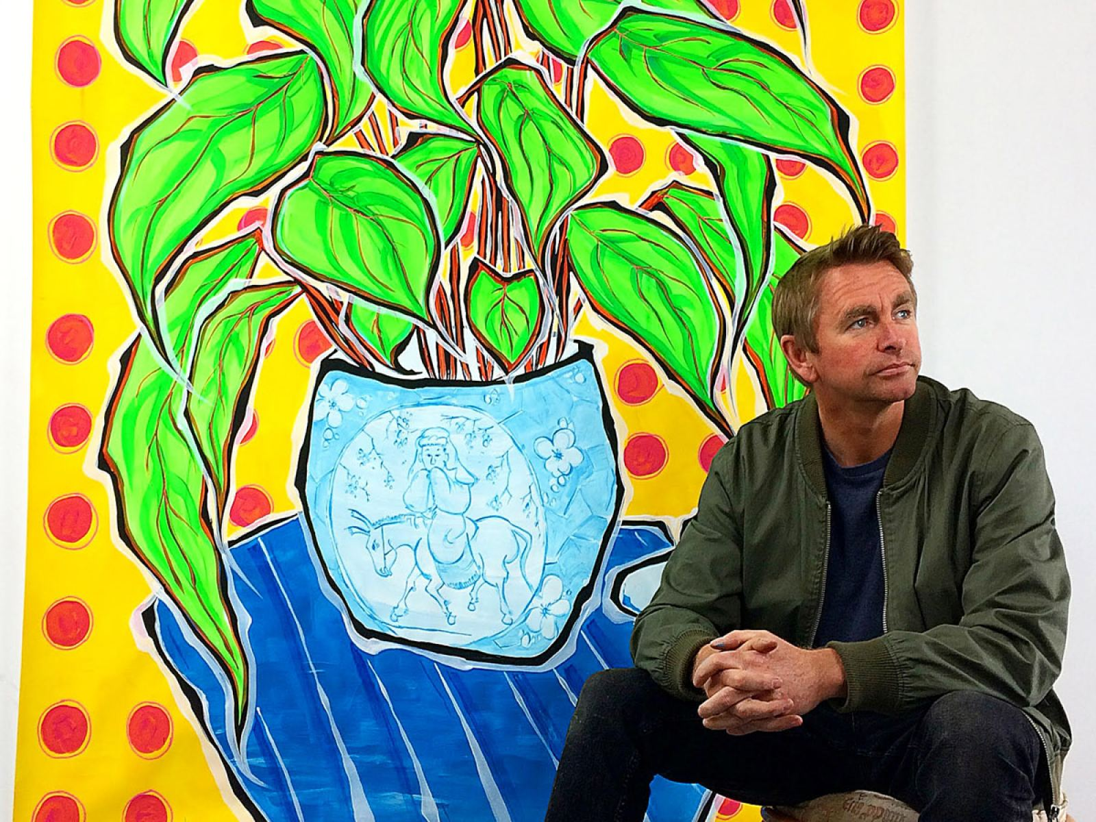 """Artist Jonjo Elliott with his painting """"Arms Raised in a V"""" from the Glass Half Full collection"""