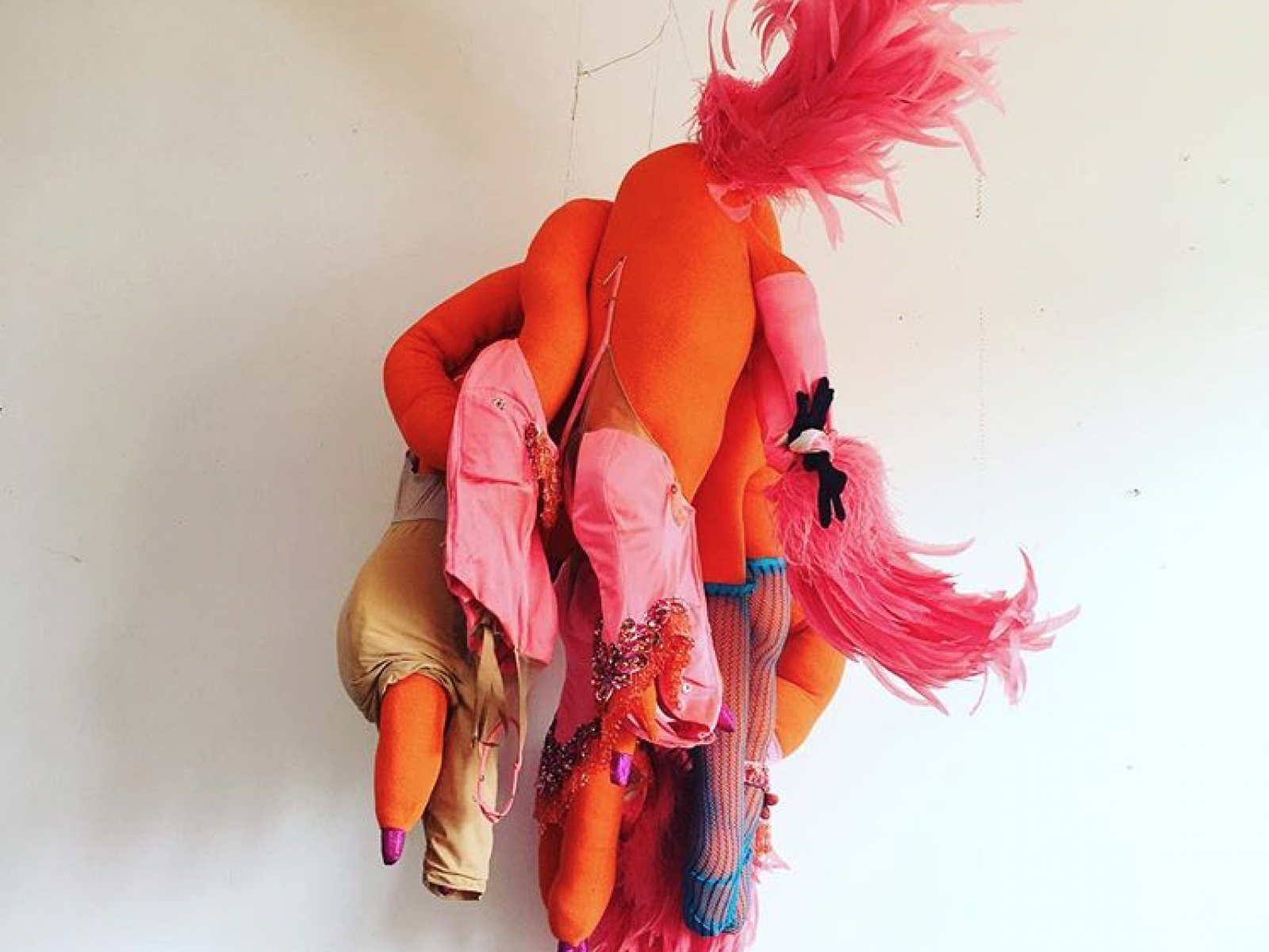 Pink and orange fabric sculpture against white background