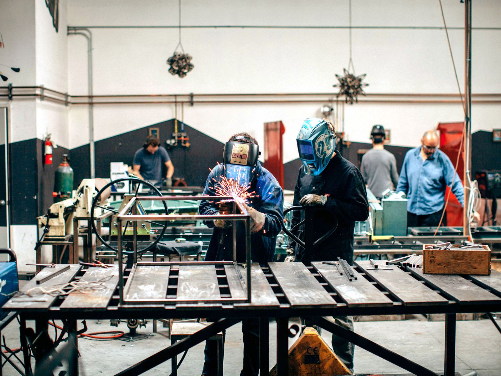 Group of people welding objects in a studio