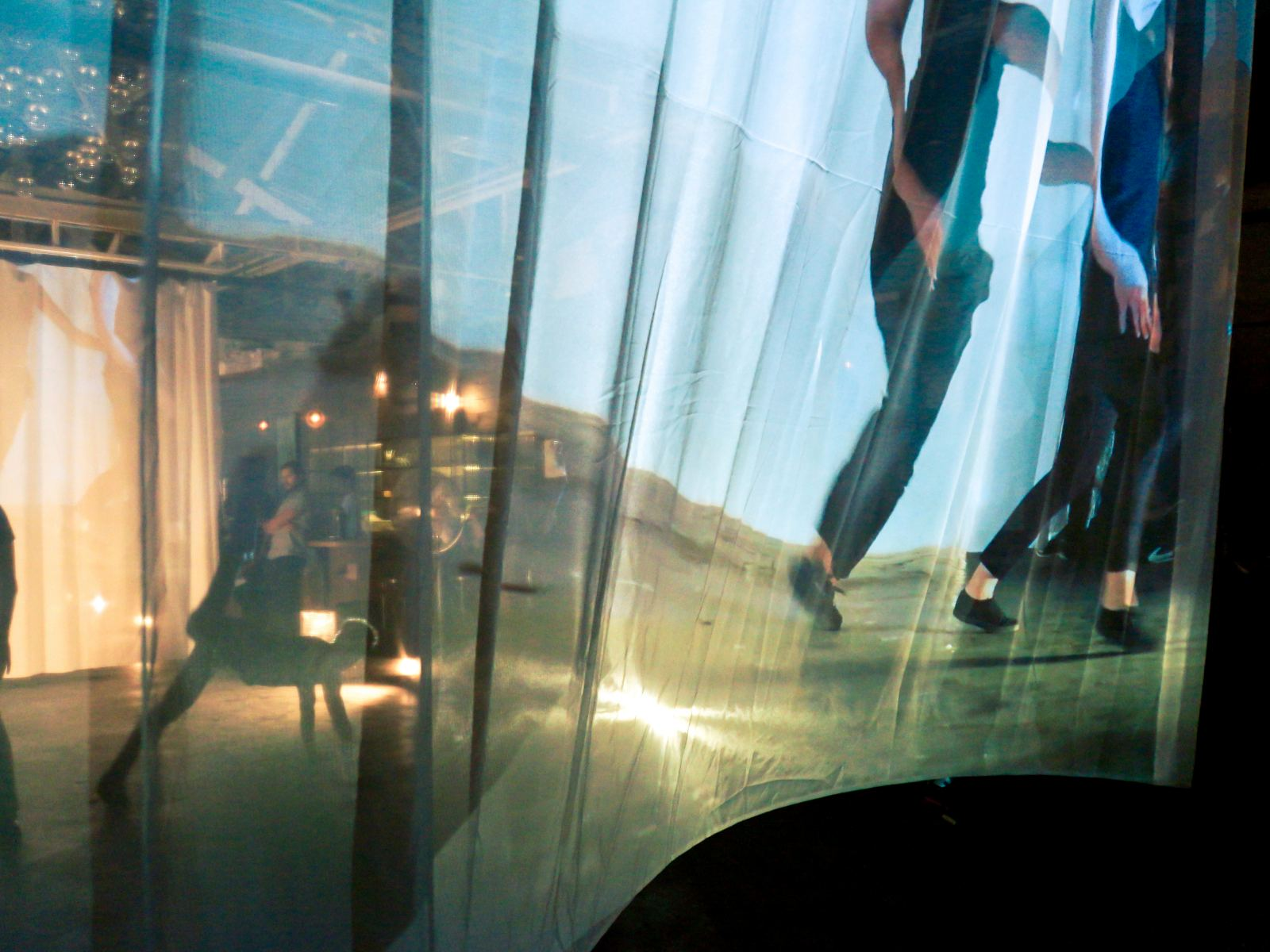 Sheer curtains reveal dancers beyond, as well as images of their movement.