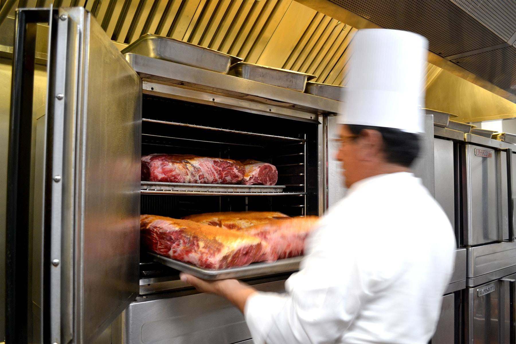 A chef loads prime rib into an oven at Lawry's The Prime Rib