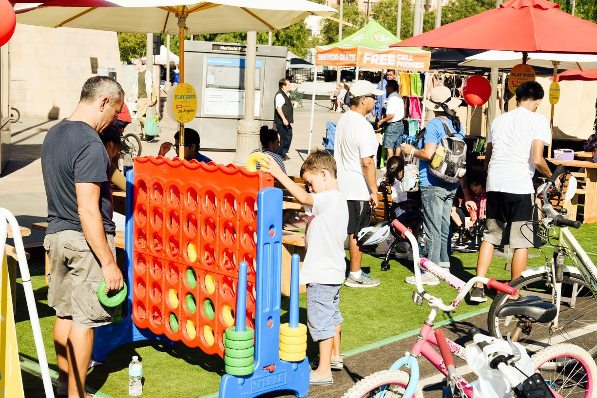 Father and son playing giant Connect Four at CicLAvia: Heart of LA Mariachi Plaza Hub