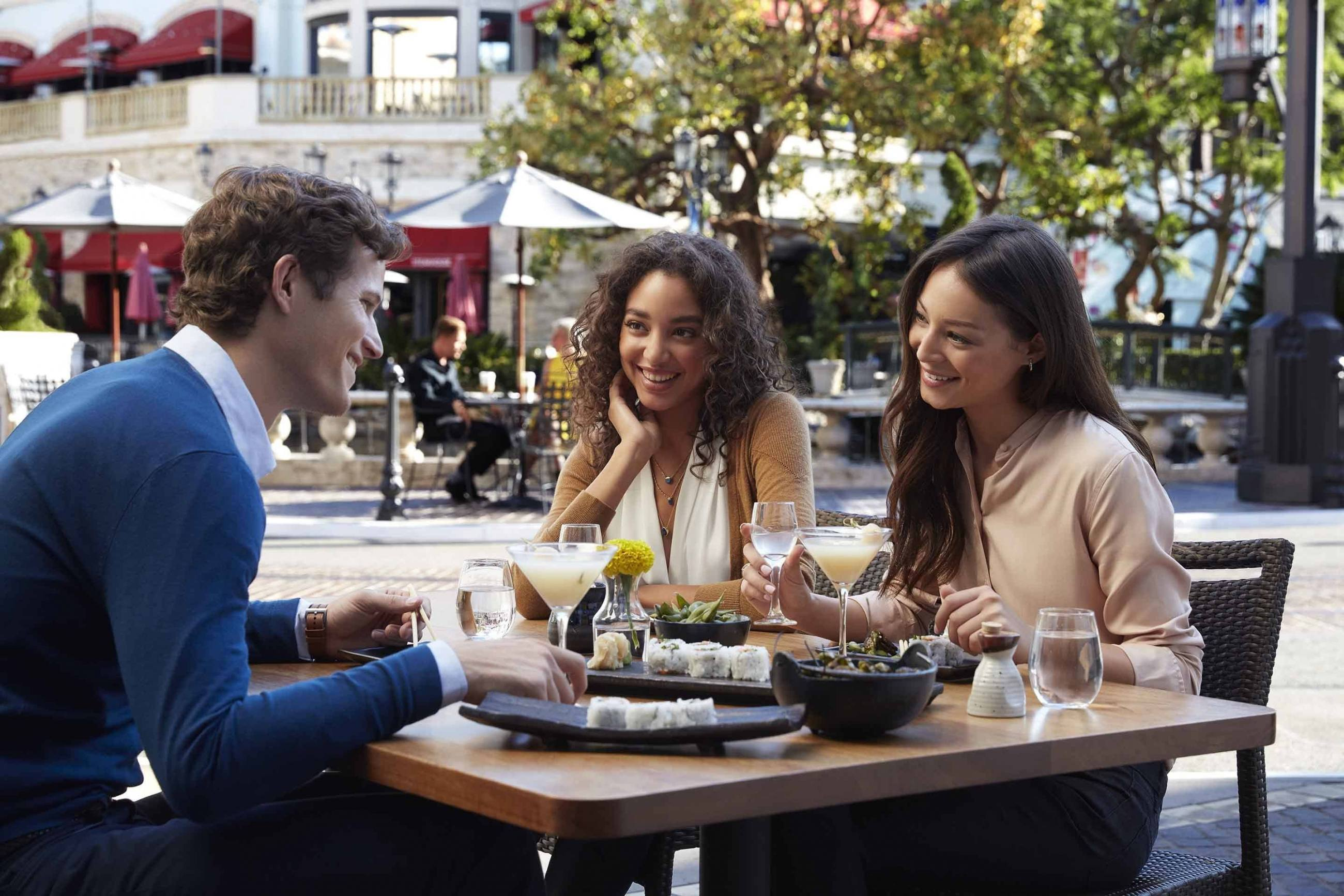 Two girls and a guy dining at The Grove
